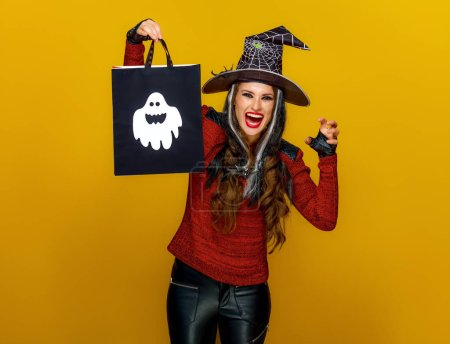 Photo for Smiling modern woman in halloween witch costume showing shopping bag and looking at camera while frightening on yellow background - Royalty Free Image