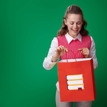 Photo for Smiling young student woman in red waistcoat looking at shopping bag with books on green background - Royalty Free Image