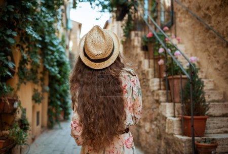 Photo pour Vue arrière de l'élégante femme touristique en robe longue et chapeau de paille marche dans la vieille ville italienne - image libre de droit