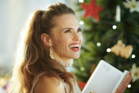 happy modern housewife with notebook near Christmas tree