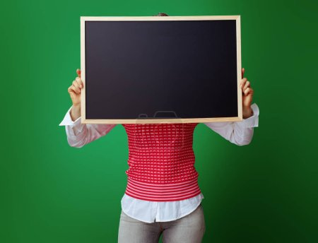 Photo for Young student woman in grey jeans and pink sleeveless shirt hiding behind blackboard against chalkboard green background. - Royalty Free Image