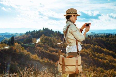Photo pour Vu de derrière jeune touriste solo en équipement de randonnée avec sac et smartphone en utilisant des applications sur la route de Toscane d'été . - image libre de droit