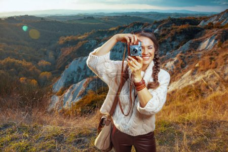 Photo for Happy adventure solo traveller woman in hiking clothes with bag taking photos with retro photo camera in the front of scenery of summer Tuscany ,Italy. - Royalty Free Image