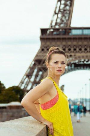 Photo pour Jeune femme sportive vêtue de fitness devant la tour Eiffel à Paris, en France . - image libre de droit