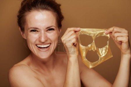 Photo pour Portrait de femme élégante heureuse montrant fraîchement retiré du visage masque cosmétique doré sur fond de bronze . - image libre de droit