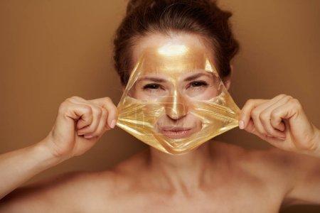 Photo pour Portrait de gaie femme moderne de 40 ans enlever masque cosmétique doré isolé sur fond brun . - image libre de droit
