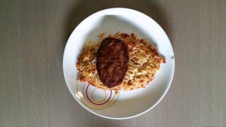Photo pour Nourriture maison, tacu tacu péruvien avec viande sur une table en bois - image libre de droit