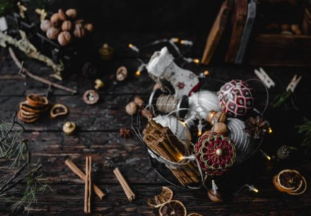 Pile of Christmas decorations and cinnamon barks in metal basket on dark wooden background