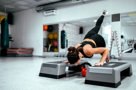 Doing a push up on a step platform with one leg up.