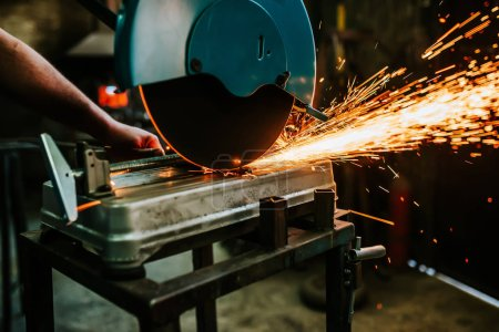 close-up photo of Worker cutting metal with grinder.
