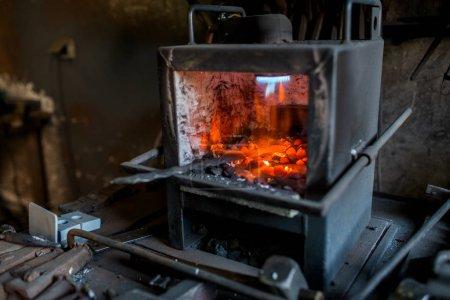Blacksmith furnace with red hot metal workpiece.