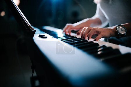 Photo pour Vue rapprochée d'une femme jouant du synthétiseur de piano . - image libre de droit