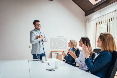 Photo for Corporate people clapping hands appreciating leader for good result. - Royalty Free Image