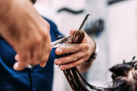 Close-up image of hairdresser cutting hair.