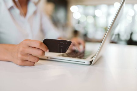 Buying online. Close-up image of female hand holding credit card and using laptop.