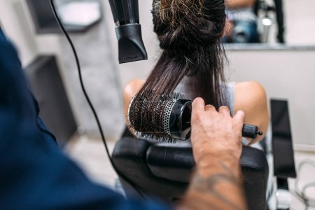 Photo pour Coiffeur séchage cheveux longs avec sèche-cheveux et brosse ronde . - image libre de droit
