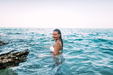 Smiling young woman standing in the sea water. Authentic reaction.