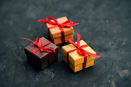 Photo pour Trois petites boîtes-cadeaux sur fond sombre . - image libre de droit