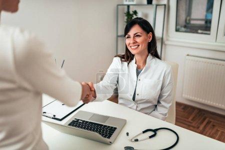Photo pour Charmante femme médecin saluant la patiente dans le bureau . - image libre de droit