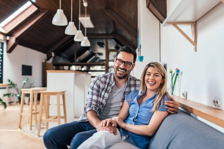 Photo for Laughing young couple sitting on the sofa at their new modern apartment. - Royalty Free Image