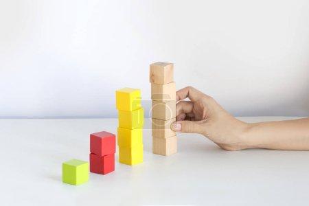 Foto de Cuadro de crecimiento de negocios y finanzas conceptuales bodegón sobre fondo blanco. Cubos de apilamiento a mano . - Imagen libre de derechos