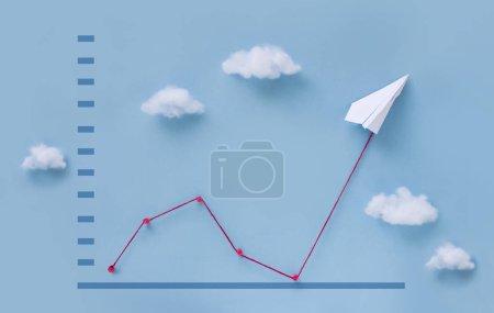 Photo pour Avion conceptuel en papier tirant la ligne du graphique de croissance du financement des entreprises vers le haut sur fond de ciel bleu . - image libre de droit