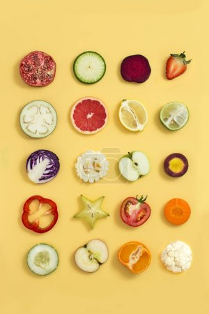 Photo for Various colourful sliced vegetables and fruits on yellow background. - Royalty Free Image