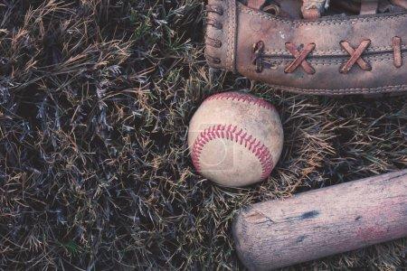 Photo pour Baseball avec chauve-souris et gant posé dans l'herbe des champs, style grunge . - image libre de droit