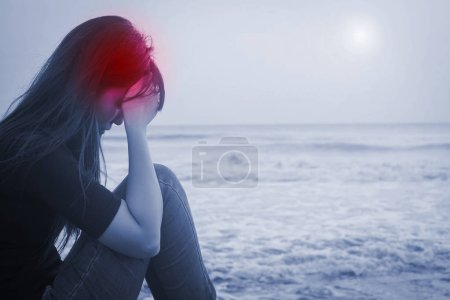 woman sitting  with  headache on  seaside