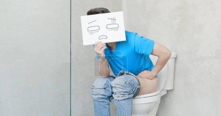 Photo pour Homme avec carte de ressentir de la douleur avec la constipation dans les wc - image libre de droit