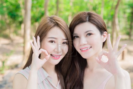 Photo for Two beauty women wearing  braces  showing  ok gestures - Royalty Free Image