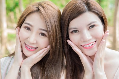 two beauty women wearing  braces  smiling  happily
