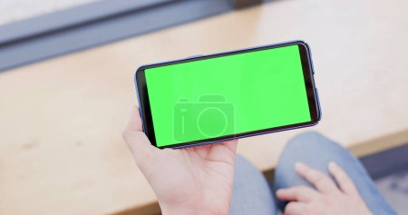woman holding  cell phone with green screen