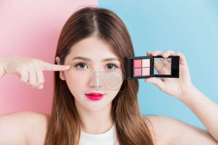 pretty girl  with  makeup palette  on a pink and blue background