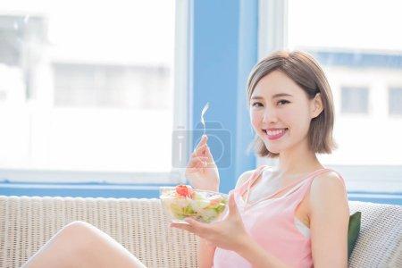 beautiful  woman eating  salad at home