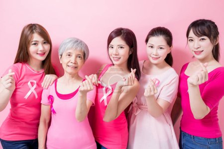 women with breast cancer prevention and show heart gesture on the pink background