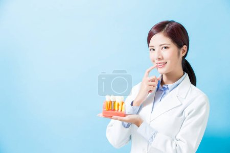 woman dentist take implant tooth and touch teeth on the blue background