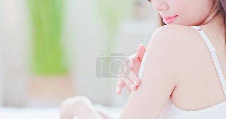 Photo pour Femme asiatique de jeune peau soins appliquer une lotion sur le bras et l'épaule à la maison - image libre de droit