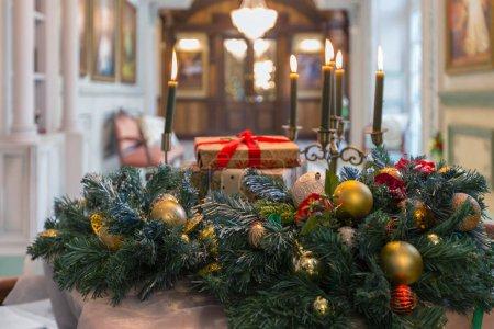 gros plan des bougies, des cadeaux et des branches de sapin décoré