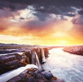 Fantastic views of Selfoss waterfall in the national park Vatnajokull. Mysterious and mystical sunset in pink - orange. Iceland