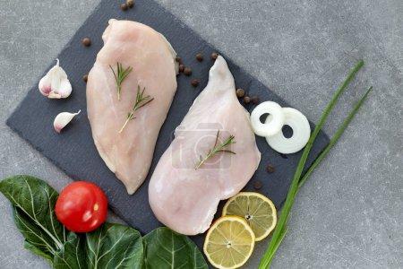 Foto de Filete de pechuga de pollo cruda con especias y ensalada de hojas sobre una mesa de piedra gris. Vista superior. Alimentos saludables. - Imagen libre de derechos