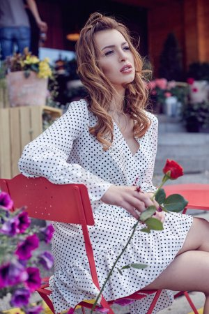 Elegant Young woman in a white dotted dress sitting in cafe terrace holding a rose flower. Girl with blossom flowers outdoors. Fashion model portrait.