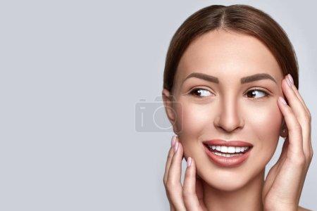 Photo pour Belle femelle avec peau propre claire, maquillage naturel et dents blanches sur fond gris. Concept de beauté et spa. Peau saine. Horizontal - image libre de droit