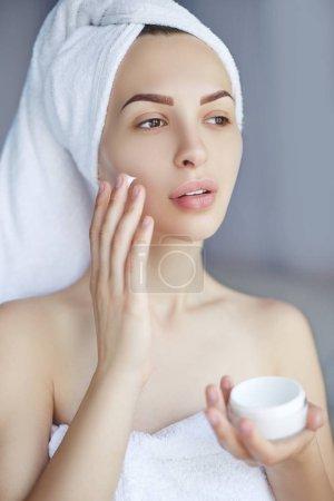 Photo pour Femme de Spa appliquant la crème pour le visage. Soins de beauté. Portrait de la belle fille avec une serviette sur sa tête, appliquer la crème pour le visage. Cosmétologie. - image libre de droit