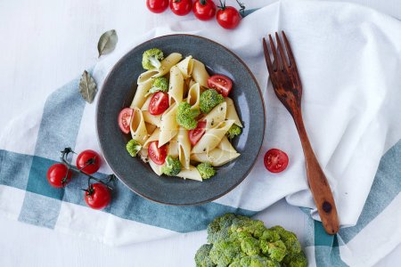 Photo for Pasta penne with broccoli on white wooden table. Healthy vegetarian food. Top view. Copy space - Royalty Free Image