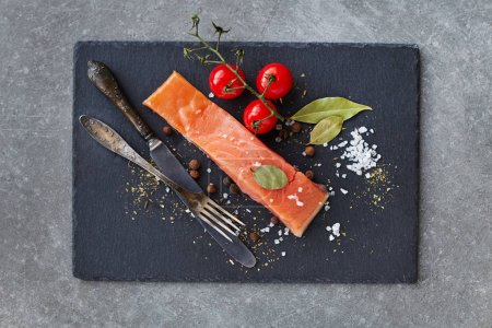 Photo for Salted Salmon. Red Fish Slice served with Spices and Cherry Tomatoes on slate over grey background. Cooking Salmon, sea food. Healthy eating concept. Top view - Royalty Free Image