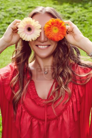 Photo pour Happy young beautiful woman in red dress closes her eyes with flowers and smiling.  Gorgeous woman portrait close-up. - image libre de droit