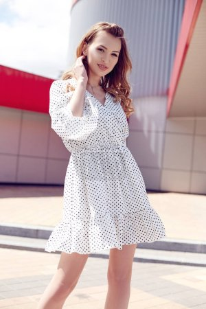 Young sexy woman in white polka dots dress