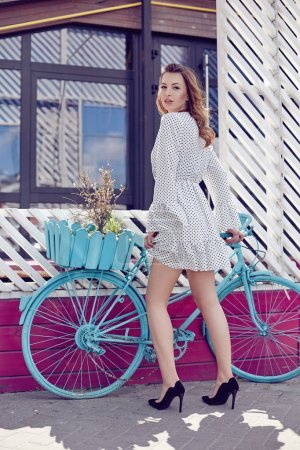 Stylish retro pin-up girl in dotted dress with retro blue bicycle