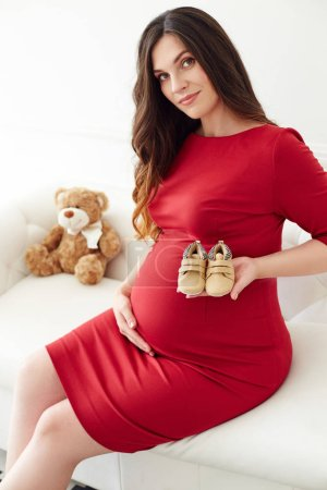 Pregnant Woman in red dress holding little baby shoes near her belly. Pregnancy concept, expectant female.